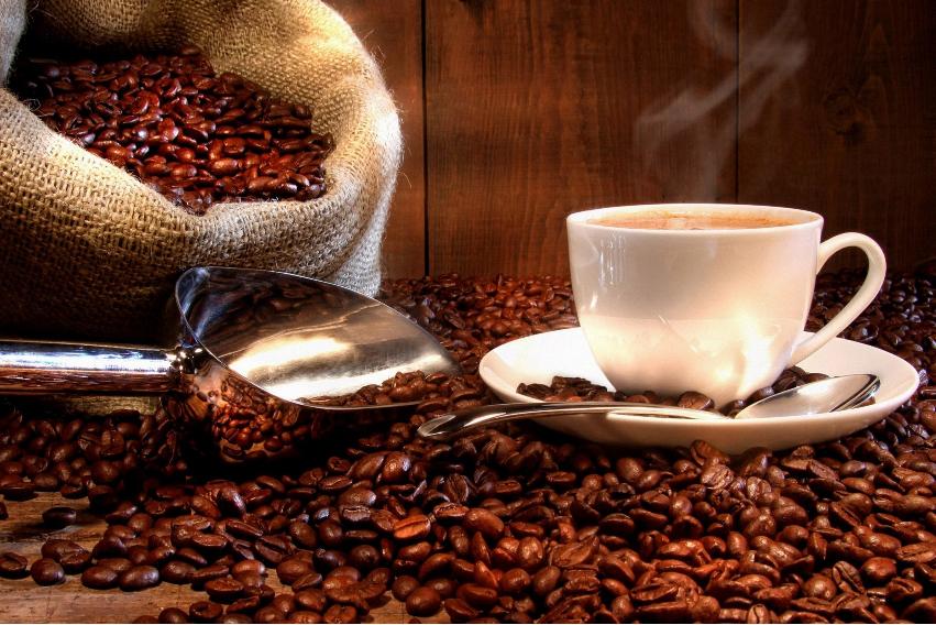 Granos de café tostado y taza de café.